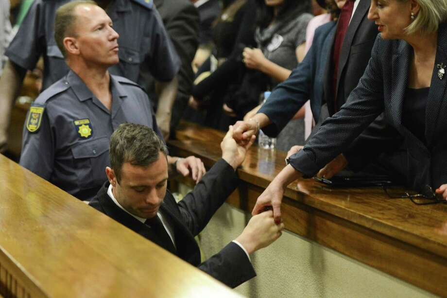 "Oscar ""Blade Runner"" Pistorius holds the hands of family members Tuesday as he is taken down to the holding cells after being sentenced to five years imprisonment for the culpable homicide killing of his girlfriend Reeva Steenkamp. He also got a three-year suspended term on a separate firearms charge. Photo: HERMAN VERWEY, Staff / AFP"