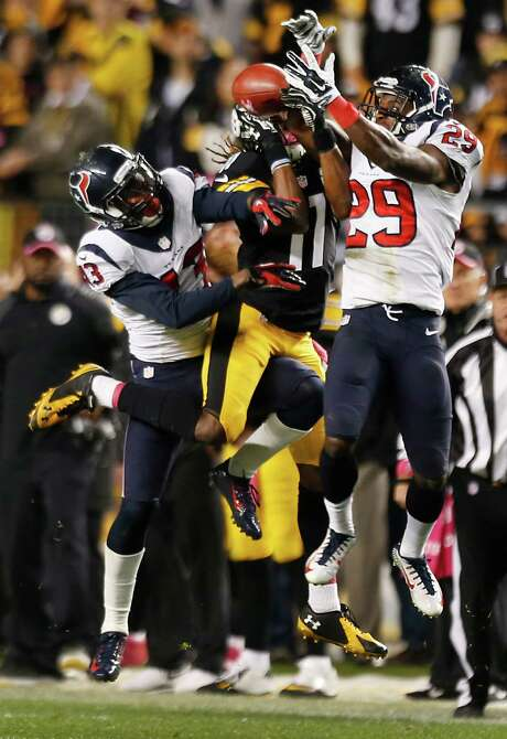 The Texans' lack of execution Monday night included failing to recover an onside kick in the final minute, with  Elbert Mack, left, and Andre Hal, right, having a shot in the air and other players bungling their chances on the ground. Photo: Brett Coomer, Staff / © 2014  Houston Chronicle
