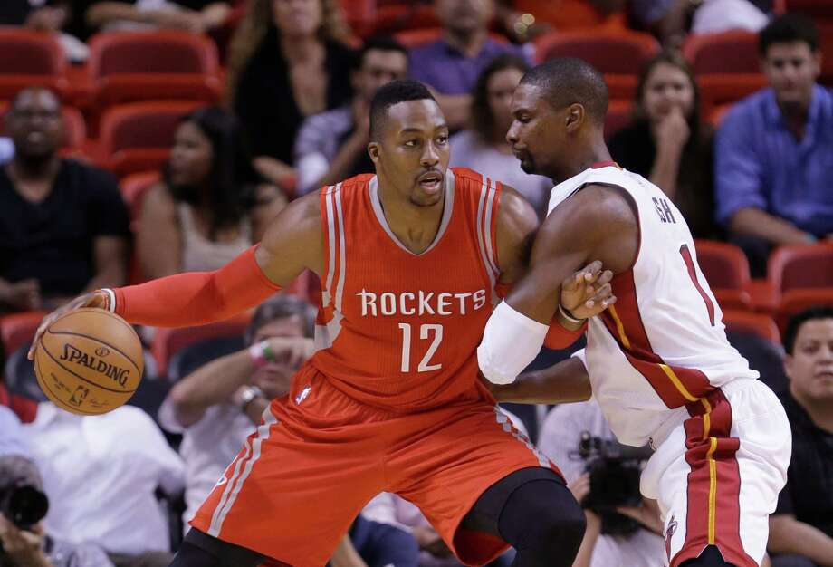 Instead of forming two-thirds of the Rockets' starting frontcourt, Dwight Howard, left, and Chris Bosh were banging into each other Tuesday night. Photo: Wilfredo Lee, STF / AP