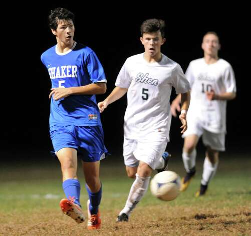 Shaker's Justin Brehm, left, passes the ball as Shen's Miles Burbank, center, defends during their soccer game on Thursday, Oct. 16, 2014, at Shenendehowa High in Clifton Park, N.Y. (Cindy Schultz / Times Union) Photo: Cindy Schultz / 10029041A