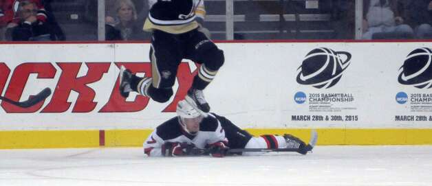 A Penguins player jumps over Brandon Burlon of the Devils during their game on Tuesday, Oct. 21, 2014, in Albany, N.Y.  (Paul Buckowski / Times Union) Photo: Paul Buckowski / 00029136A