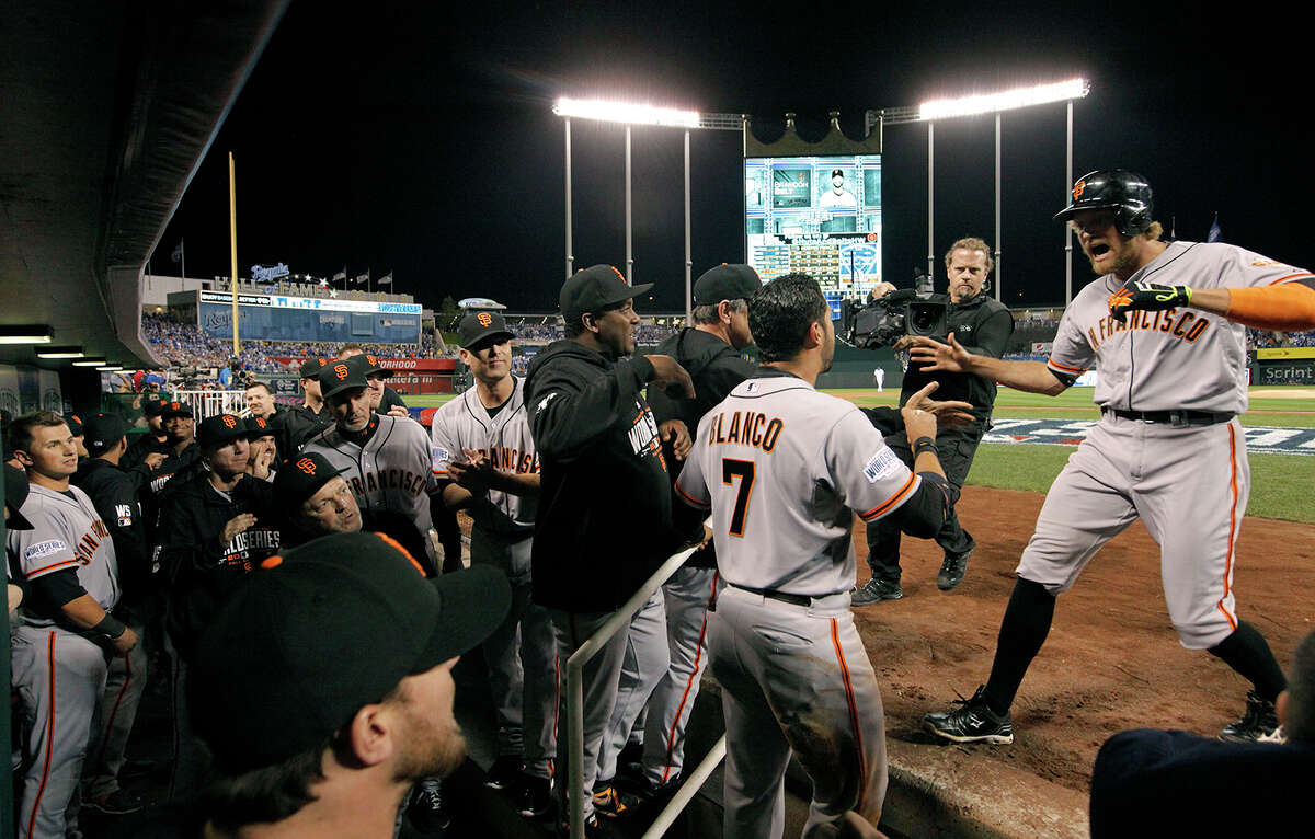 Hunter Pence, 8 (right) returns to the dugout after his 2 run home run in the first inning, as the San Francisco Giants went on to win 7-1 over the Kansas City Royals in game one of the World Series at Kauffman Stadium in Kansas City, Mo., on Tuesday Oct.21, 2014.
