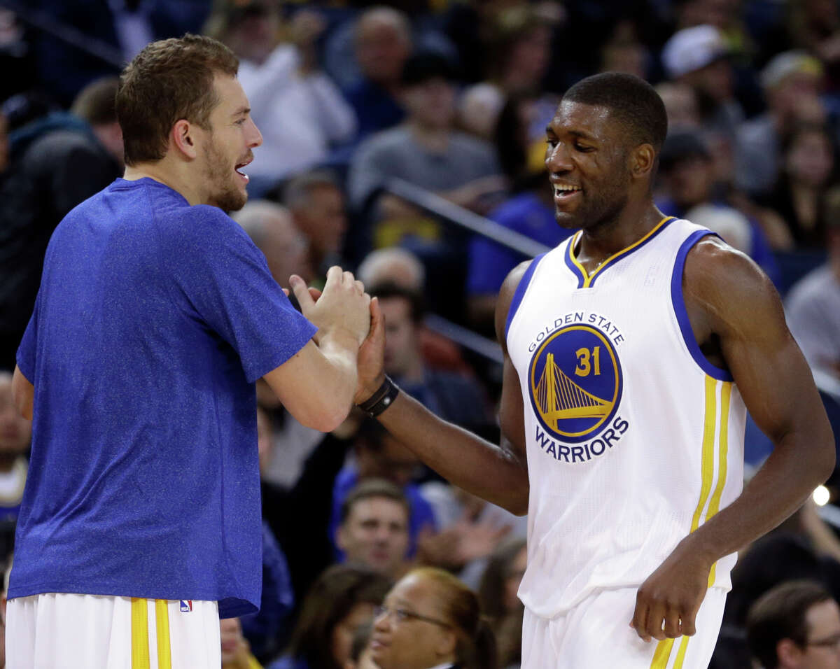 Warriors forward David Lee (left) congratulates Festus Ezeli in the first half after the center got his first playing time in 17 months. Ezeli had knee surgery, then had shin inflammation.