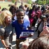 Gubernatorial candidate Wendy Davis takes pictures with students at  Texas Southern University during a rally encouraging them to get out and vote on Tuesday, Oct. 21, 2014, in Houston. Students then boarded buses and headed to an early voting site to cast their ballots.