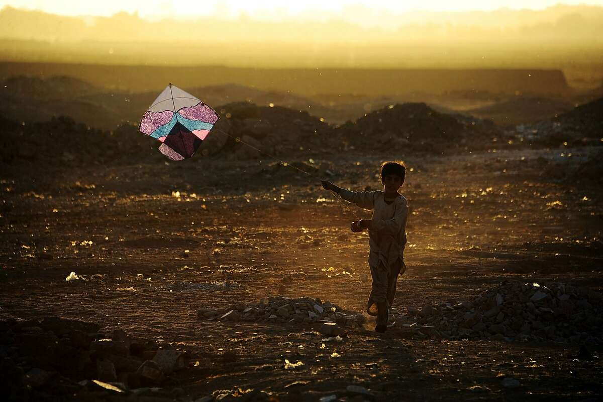 TOPSHOTS In this photograph taken on October 20,2014, an Afghan child plays with a kite on the outskirts of Herat. Afghanistan's economy has improved significantly since the fall of the Taliban regime in 2001 largely because of the infusion of international assistance. Despite significant improvement in the last decade the country is still extremely poor and remains highly dependent on foreign aid. AFP PHOTO/AREF KARIMIAref Karimi/AFP/Getty Images
