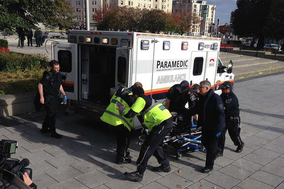 Police and paramedics transport a wounded Canadian soldier on October 22, 2014 in Ottawa, Ontario. Canadian police backed by armored vehicles surrounded parliament in Ottawa on Wednesday after a soldier was shot while guarding a nearby monument. Witnesses said they saw a gunman running to the parliament building after the shooting. Heavily armed police raced to seal off the building and the office of Canadian Prime Minister Stephen Harper.