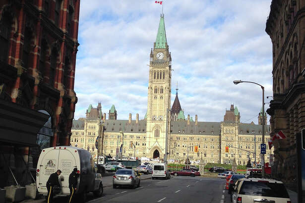 This October 22, 2014 photo shows the Parliament building, and police after a shooting at the National War Memorial in Ottawa, Canada. Parliament Hill's Centre Block is in lockdown after a Canadian soldier standing guard at the National War Memorial in Ottawa was shot by an unknown gunman and there are reports of gunfire inside the halls of Parliament.