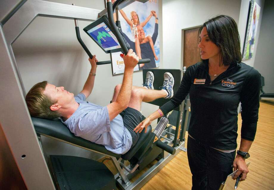 Courtney Bastien trains Richard Hankamer at the Exercise Coach during one of his two 20-minute weekly sessions. Photo: Cody Duty, Staff / © 2014 Houston Chronicle