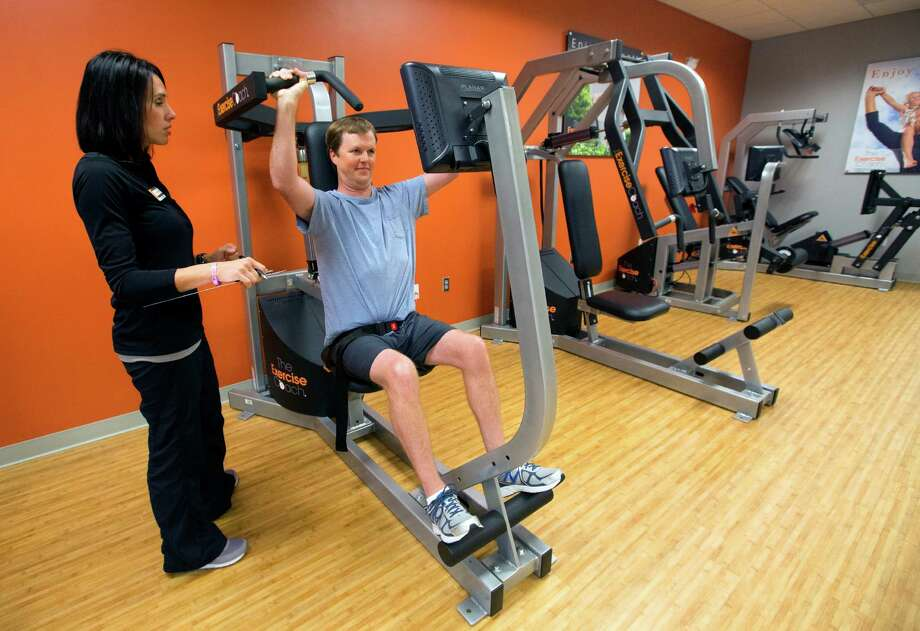 Courtney Bastien, left, trains Richard Hankamer, right, at Exercise Coach, Tuesday, Oct. 14, 2014, in Houston. The program involves 20-minute sessions for clients ranging 2-3 times per week. (Cody Duty / Houston Chronicle) Photo: Cody Duty, Staff / © 2014 Houston Chronicle
