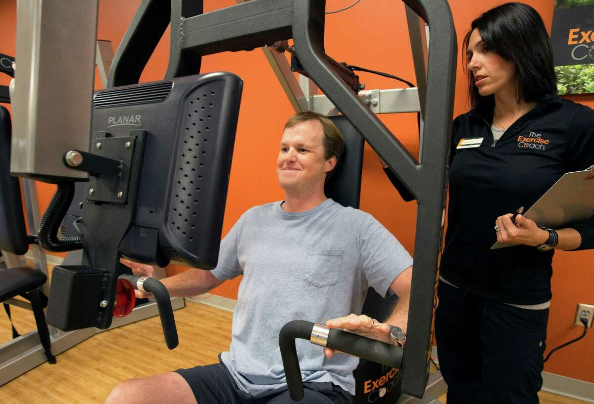 Courtney Bastien, right, trains Richard Hankamer, left, at Exercise Coach, Tuesday, Oct. 14, 2014, in Houston. The program involves 20-minute sessions for clients ranging 2-3 times per week. (Cody Duty / Houston Chronicle)