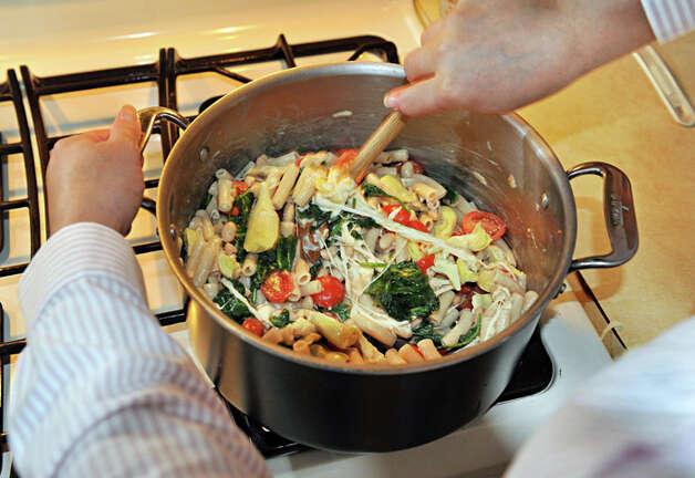 Elizabeth Barbone mixes ingredients for her gluten-free garlic pasta in her kitchen. Photo: John Carl D'Annibale/Women@Work / Women@Work Magazine