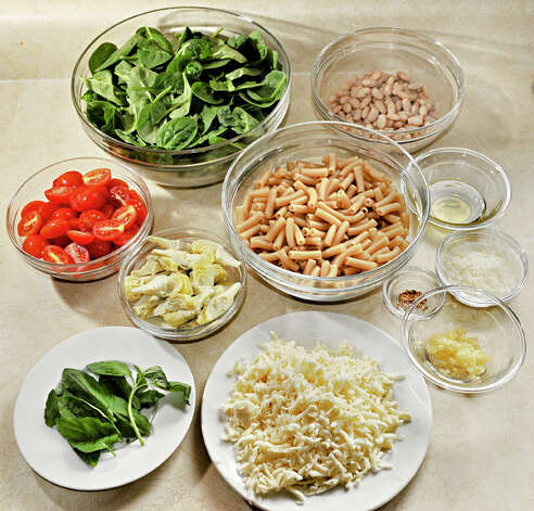 Ingredients for Elizabeth Barbone's 25 Minute Garlicky Pasta: clockwise from top, Spinach, Cannellini beans, gluten free Penne pasta, olive oil, grated Parmesan cheese, red pepper flakes, minced garlic, mozzarella cheese, fresh basil, artichoke hearts, grape tomatoes. Photo: John Carl D'Annibale/Women@Work / Women@Work Magazine