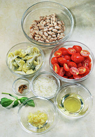 Ingredients for Elizabeth Barbone's 25 Minute Garlicky Pasta: clockwise from top, Cannellini beans, grape tomatoes, grated Parmesan cheese,  olive oil, minced garlic, fresh basil, red pepper flakes, and artichoke hearts. Photo: John Carl D'Annibale/Women@Work / Women@Work Magazine