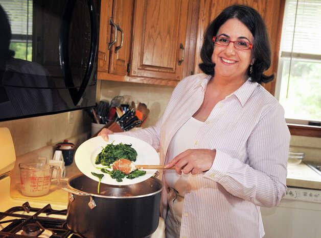 Elizabeth Barbone adds cooked spinach to her gluten-free garlic pasta in her kitchen. Photo: John Carl D'Annibale/Women@Work / Women@Work Magazine