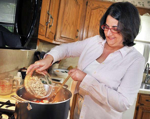Elizabeth Barbone adds Cannellini beans to her gluten-free garlic pasta in her kitchen. Photo: John Carl D'Annibale/Women@Work / Women@Work Magazine