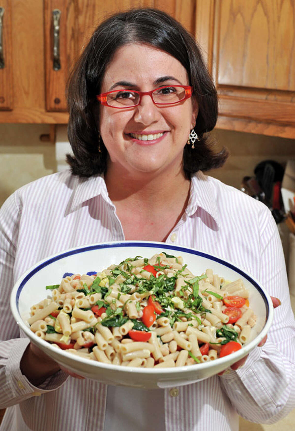 Elizabeth Barbone holds a bowl of her gluten-free garlic pasta in her kitchen.