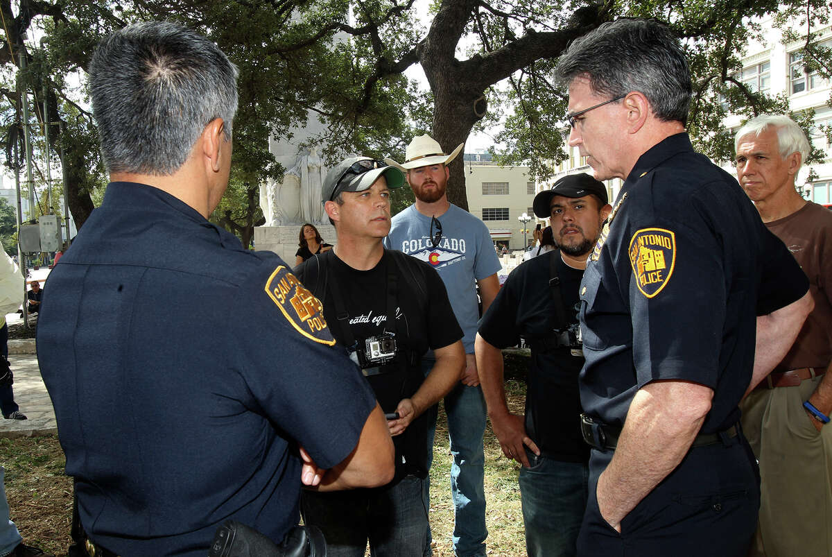 Mark Harrington, (center) national Director of Created Equal, speaks with San Antonio police chief William McManus about setting up equipment in Alamo Plaza that would display abortion images.