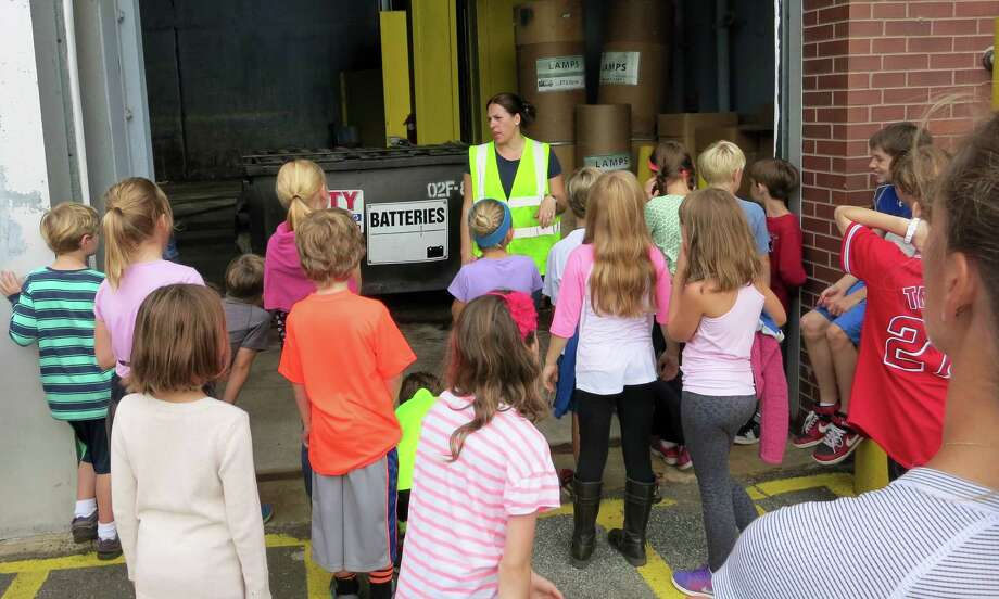 Darien Environmental Group volunteer Allison Stolar explains the importance of recycling used household batteries and light bulbs. Students also saw where to recycle single stream items, electronics, large plastics, motor oil, scrap metal, textiles, yard waste and toured the Swap Shop. Photo: Contributed Photo, Contributed / Darien News Contributed