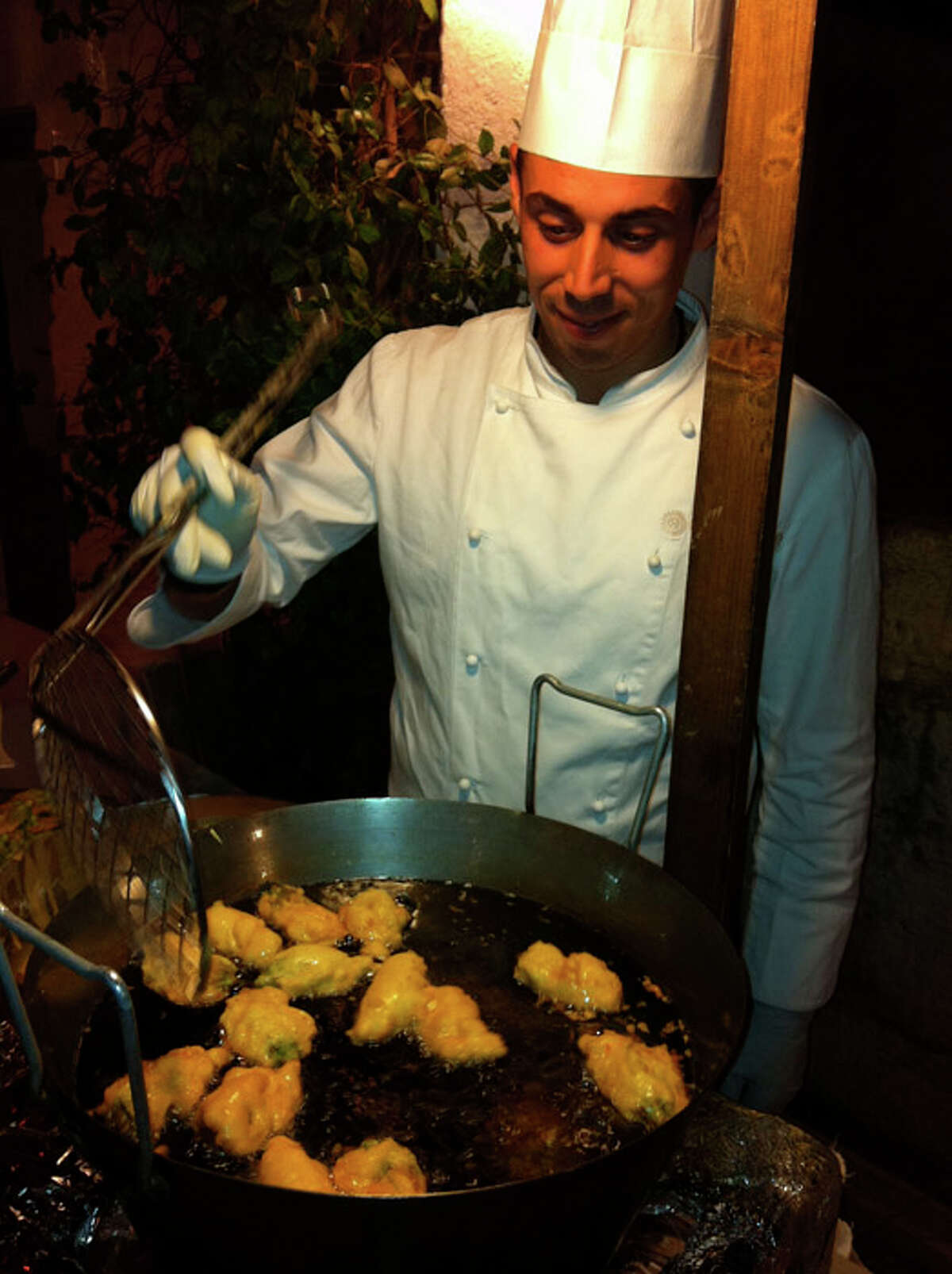 A chef prepares fried dough (to be drizzled with honey) at Masseria Torre Coccaro