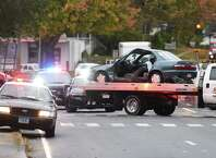 A car is towed away from the scene of a crash at the intersection of Grassy Plain Street and Whitney Road in Bethel, Conn. Wednesday, Oct. 22, 2014.