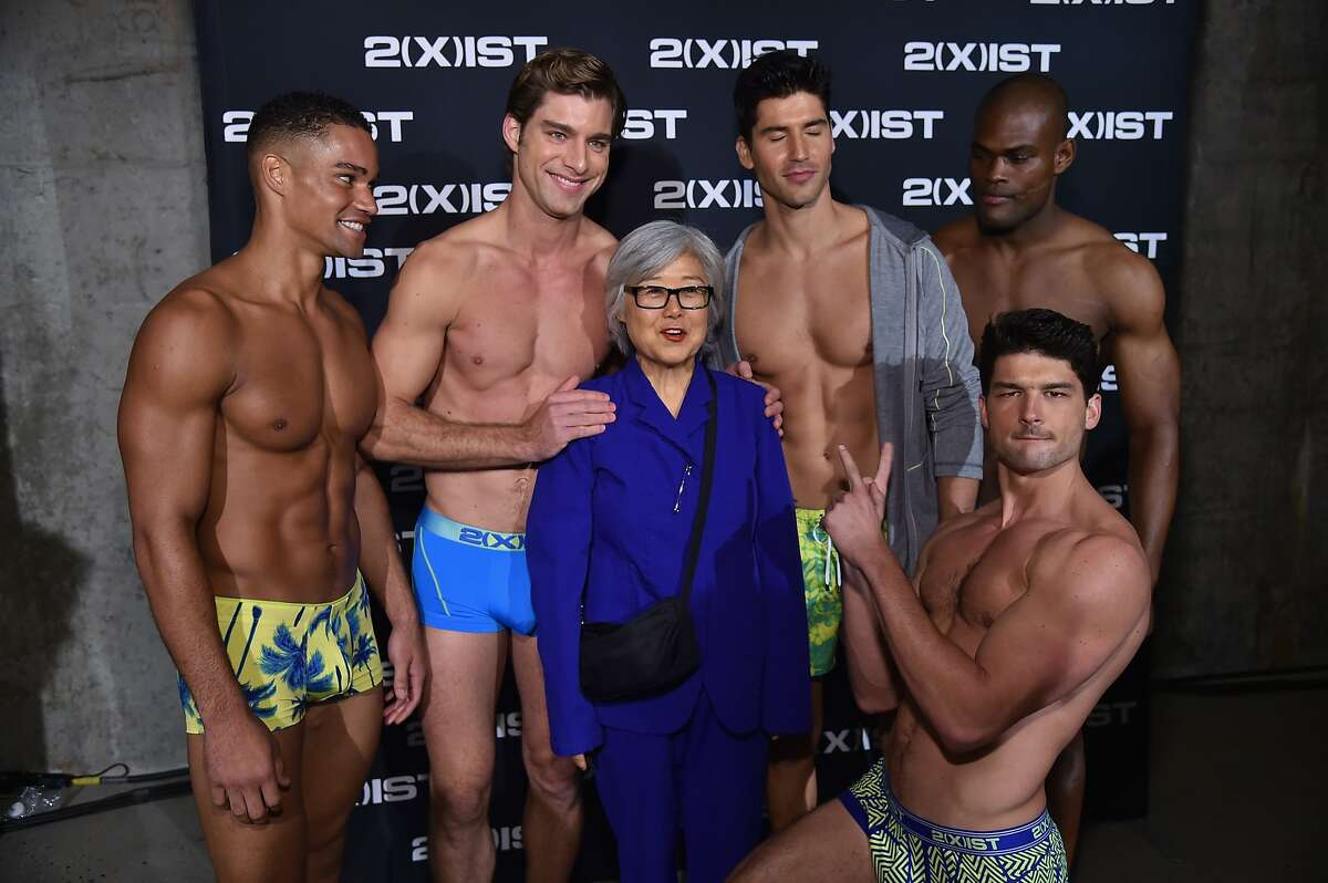 DREAMS DO COME TRUE! A guest poses with hunky models backstage during 2(X)IST Spring/Summer 2015 Runway Show in New York City.