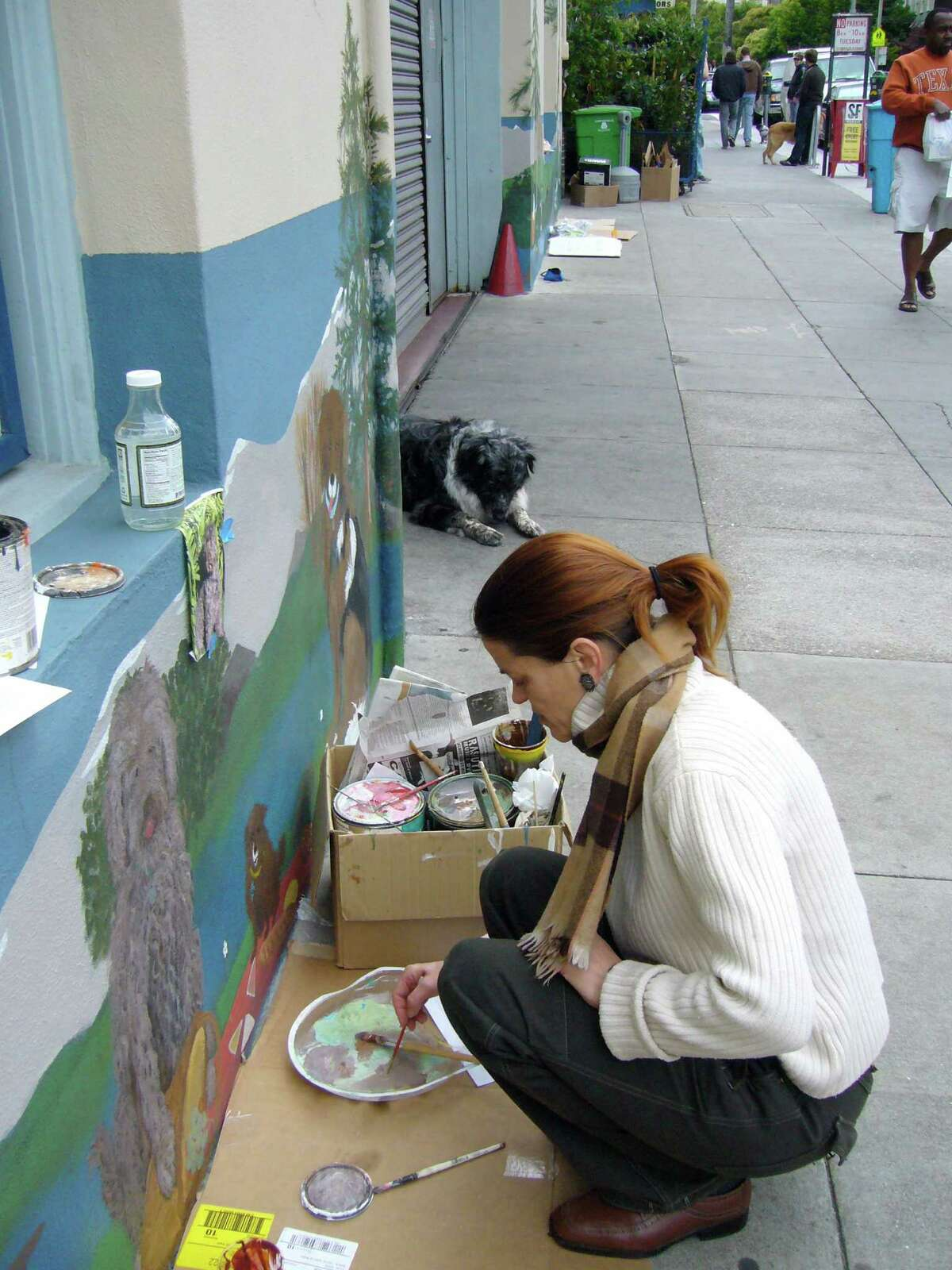 Artist Angela Tirrell works on the Cole Valley Animal Picnic Mural at 930 Cole St. in S.F.