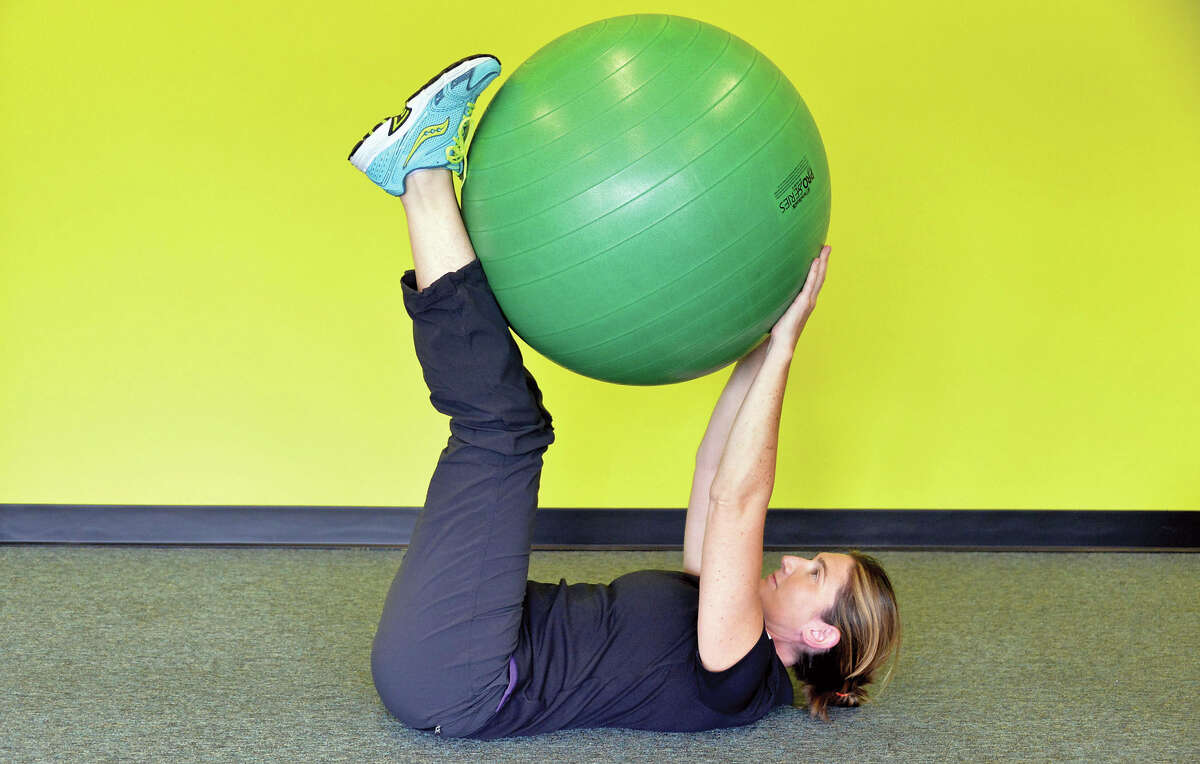 1. Begin lying on your back with your hands and feet elevated and a stability ball pressed between them.