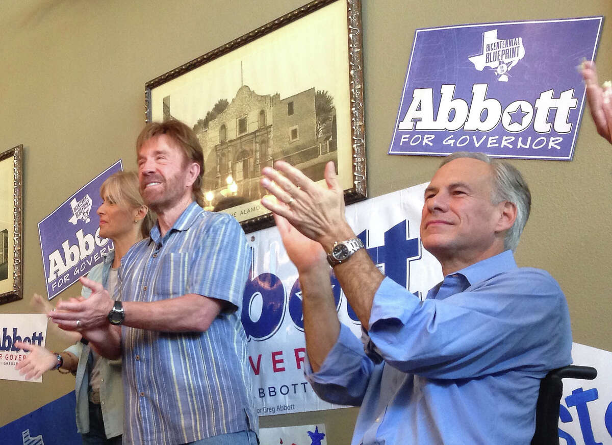 Republican gubernatorial candidate Greg Abbott, right, speaks as television star Chuck Norris and his wife, Gena, stand by during an event at the Casa Rio restaurant on the Riverwalk in San Antonio Texas on Wednesday, October 22, 2014.