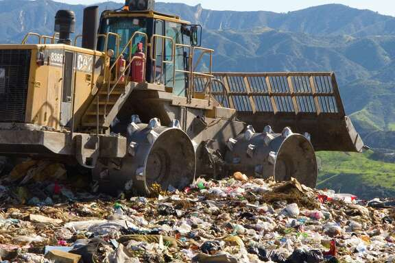 A landfill compactor adds waste to a landfill.