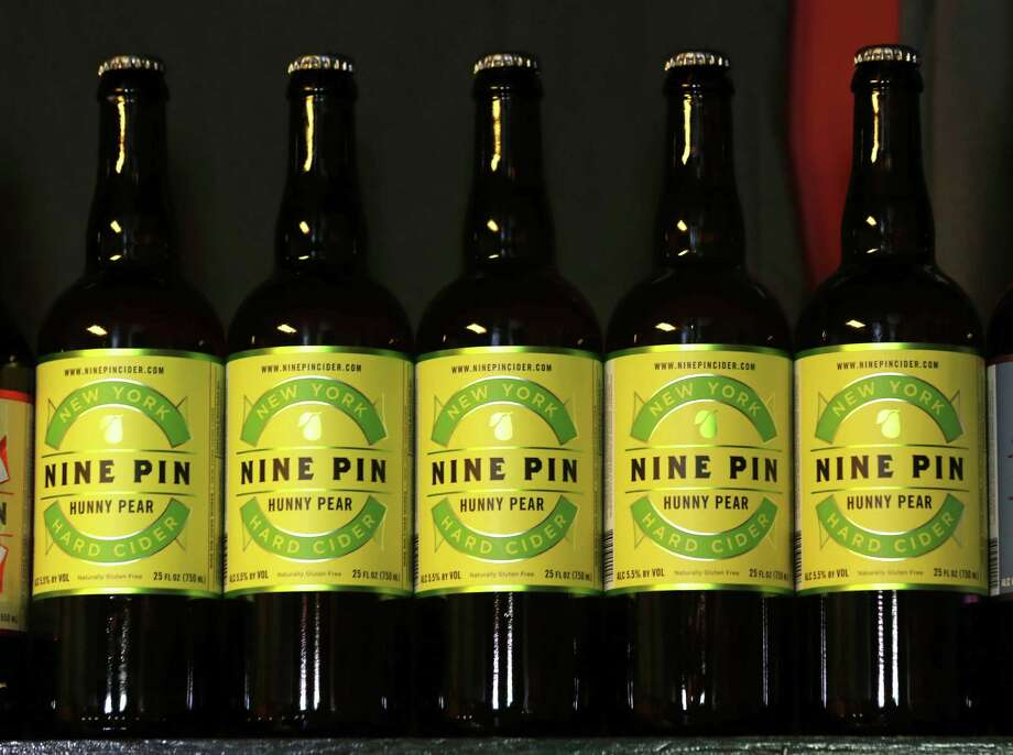 In this Oct. 3, 2014 photo, bottles of Nine Pin hard cider are lined on a shelf in the tasting room at Nine Pin Cider Works in Albany, N.Y. Apple growers are tapping into the hard cider revenue stream after sales of hard cider in the U.S. have tripled over the last three years to $1.3 billion in 2013. (AP Photo/Mike Groll)  ORG XMIT: MER2014101600443249 Photo: Mike Groll / AP