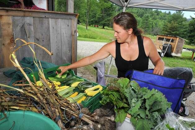 Eliza Winters unloads squash she just harvested at Hill Hollow Farm on Thursday, Aug, 1, 2013 in Petersburg, N.Y.  (Lori Van Buren / Times Union) ORG XMIT: MER2013080512161821 Photo: Lori Van Buren / 00023341A