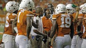 Texas head coach Charlie Strong with his players during an NCAA college football game against Iowa State in Austin, Texas, Saturday, Oct. 18, 2014. (AP Photo/Michael Thomas)