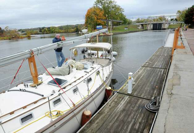 Pierre Landry of Montreal, Canada fixes something on his vessel's mast while navigating the Erie Canal during a vacation with his wife in the Bahamas Wednesday, Oct. 22, 2014, in Waterford, N.Y. There was a dedication ceremony in which the New York State Barge Canal is listed on the National Register of Historic Places at the Erie Canalway National Heritage Corridor, Visitor Center. (Lori Van Buren / Times Union) Photo: Lori Van Buren / 00029089A
