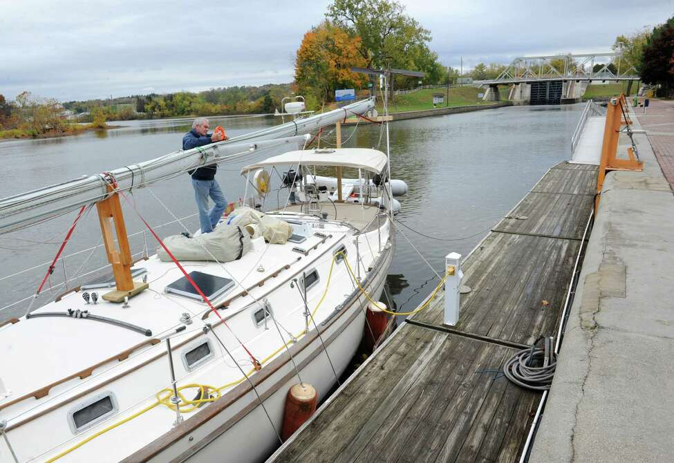 Pierre Landry of Montreal, Canada fixes something on his vessel's mast while navigating the Erie Canal during a vacation with his wife in the Bahamas Wednesday, Oct. 22, 2014, in Waterford, N.Y. There was a dedication ceremony in which the New York State Barge Canal is listed on the National Register of Historic Places at the Erie Canalway National Heritage Corridor, Visitor Center. (Lori Van Buren / Times Union)