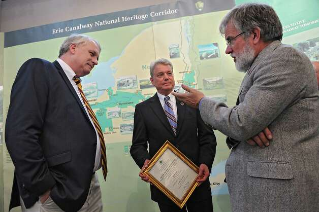 Brian U. Stratton, director, NYS Canal Corporation, center, holds a certificate from the NYS Office of Parks, Recreation and Historic Preservation while talking to Paul Loether, National  Register Chief, National Park Service, left, and Duncan Hay, historian with Erie Canalway National Heritage Corridor during a dedication ceremony in which the New York State Barge Canal is listed on the National Register of Historic Places at the Erie Canalway National Heritage Corridor, Visitor Center Wednesday, Oct. 22, 2014 in Waterford, N.Y.  (Lori Van Buren / Times Union) Photo: Lori Van Buren / 00029089A