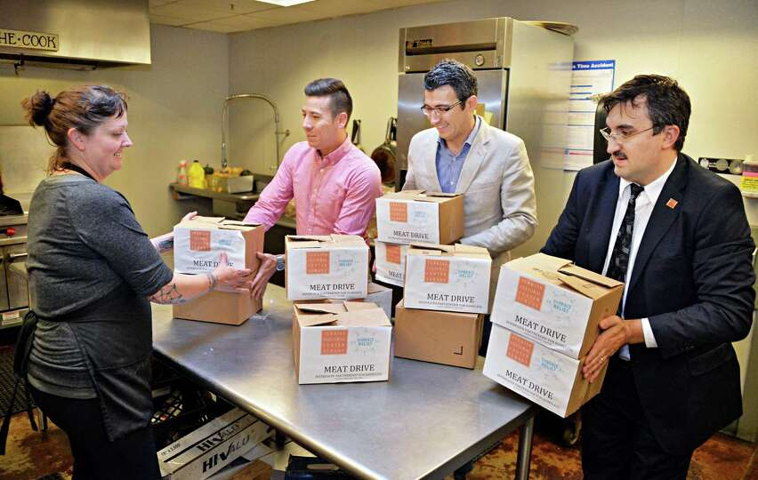 Shelter cook Sarah Fish, left, and Eric Guzman of Albany Emergency Center receive100 pounds of packa