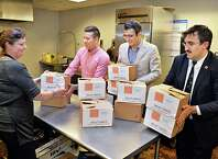 Shelter cook Sarah Fish, left, and Eric Guzman of Albany Emergency Center receive100 pounds of packaged beef cutlets from Bilal Alp and Veysel Ucan, right, of Turkish Cultural Center Albany for their Meat Drive, dedicated to the Feast of Sacrifice (Eid al Adha) in partnership with Embrace Relief Foundation Wednesday Oct. 22, 2014, in Albany, NY.  (John Carl D'Annibale / Times Union)