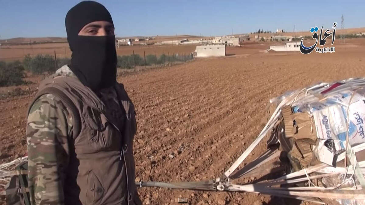 This image was taken from a video released by the SITE Intelligence Group, an organization that analyzes international terrorists, the global jihadist network and terrorism financing. In it, an Islamic State fighter appears to be showing weapons and supplies the U.S. military attempted to airdrop to Kurdish fighters in Syria. (Video screen grab)