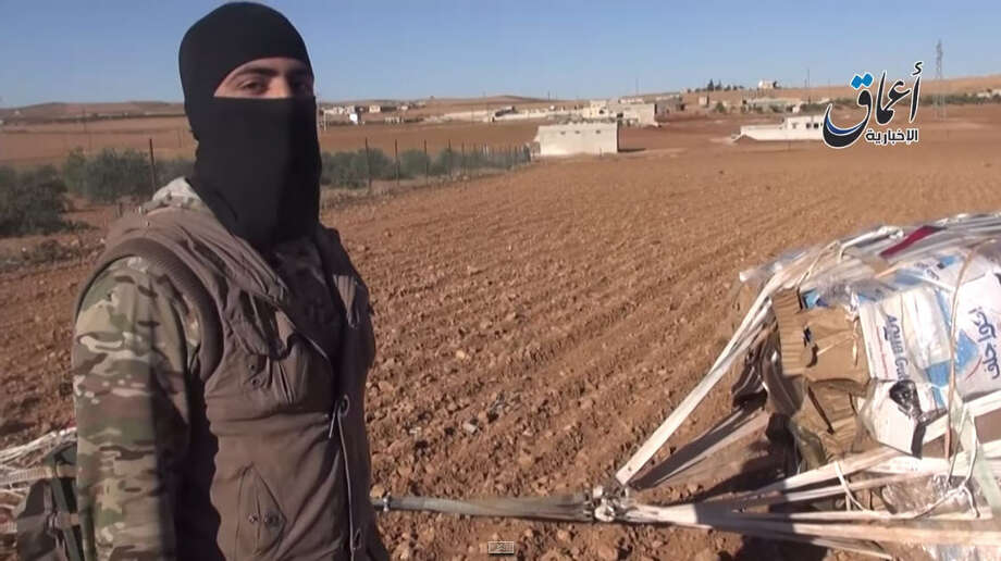 This image was taken from a video released by the SITE Intelligence Group, an organization that analyzes international terrorists, the global jihadist network and terrorism financing. In it, an Islamic State fighter appears to be showing weapons and supplies the U.S. military attempted to airdrop to Kurdish fighters in Syria. (Video screen grab) Photo: Video Released By The SITE Intelligence Group
