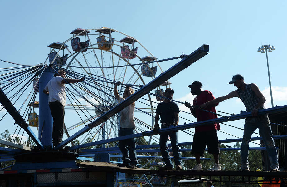 Workers attach long braces to a central spire as they construct a carousel Wednesday afternoon. Crews worked to prepare rides and vendors set up their stalls at the site of the Lumberton Village Creek Festival on Wednesday afternoon. The festival, which will be open from Thursday to Sunday, will feature more than 20 rides and attractions, and around 25 food vendors. Entry will be free, but parking is $5 per vehicle. Photo taken Wednesday 10/22/14 Jake Daniels/@JakeD_in_SETX Photo: Jake Daniels / ©2014 The Beaumont Enterprise/Jake Daniels