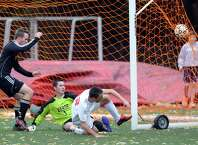 At right, Alejandro MacLean of Greenwich slides on the ground in front of the Fairfield Warde goal as he watches his shot hit the back of the net for a goal beating Fairfield Warde keeper Michael Lerman, center, for the third goal of the game during first half action in the boys high school soccer match between Greenwich High School and Fairfield Warde High School at Greenwich, Wednesday, Oct. 22, 2014. At left, following up on the play is Hunter Rempe of Fairfield Warde. Greenwich won the match over Fairfield Warde, 5-1.