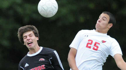 Fairfield Warde's Dylan Reilly (#20), left, and Bernardo Franca (#25) of Greenwich, both go for the header during the boys high school soccer match between Greenwich High School and Fairfield Warde High School at Greenwich, Wednesday, Oct. 22, 2014. Greenwich won the match over Fairfield Warde, 5-1.