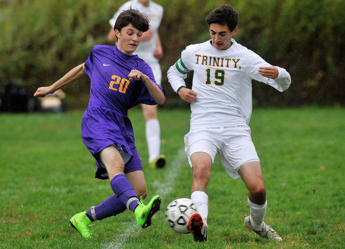 Westhill's Luca Mastrogiacomo's shot on goal is blocked by Trinity Catholic's Jack Farrell during their soccer game at Trinity Catholic High School in Stamford, Conn., on Wednesday, Oct. 22, 2014. Westhill won, 4-0.