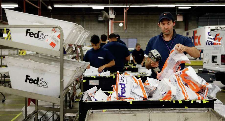 In this July 9, 2014 photo, David Demeter sorts packages at the FedEx Express station in Nashville, Tenn. FedEx on Wednesday, Oct. 22, 2014 forecast that deliveries between Thanksgiving and Christmas Eve will rise 8.8 percent over last year, to 290 million shipments. That's a more subdued forecast than a year ago, when FedEx predicted 13 percent growth for the season. (AP Photo/Mark Humphrey) ORG XMIT: NYBZ182 Photo: Mark Humphrey / AP