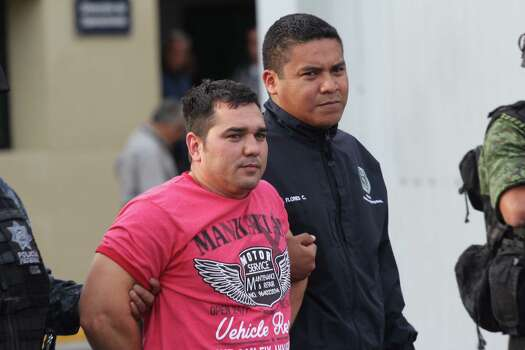Juan Manuel Rodriguez a leader of Gulf Cartel, wearing red shirt, is shown to the press by the Mexican Authorities in Mexico City, Sunday, May 25, 2014. An official for the U.S. government tells The Associated Press that Rodriguez was the Gulf Cartel's commander along the Rio Grande and was competing for control of the gang's operations in all of Tamaulipas state. (AP Photo/Luis Barron Tinajero) Photo: Luis Barron Tinajero, Associated Press / AP