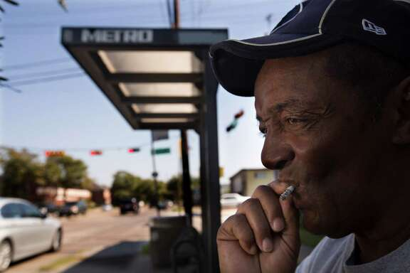 """Larry Moore smokes while waiting for a bus at Richmond and Hazard on Wednesday. """"I can understand why people wouldn't like the smoke,"""" Moore said. Metro could expand its smoking ban to uncovered bus stops and park and ride lots in the new code."""