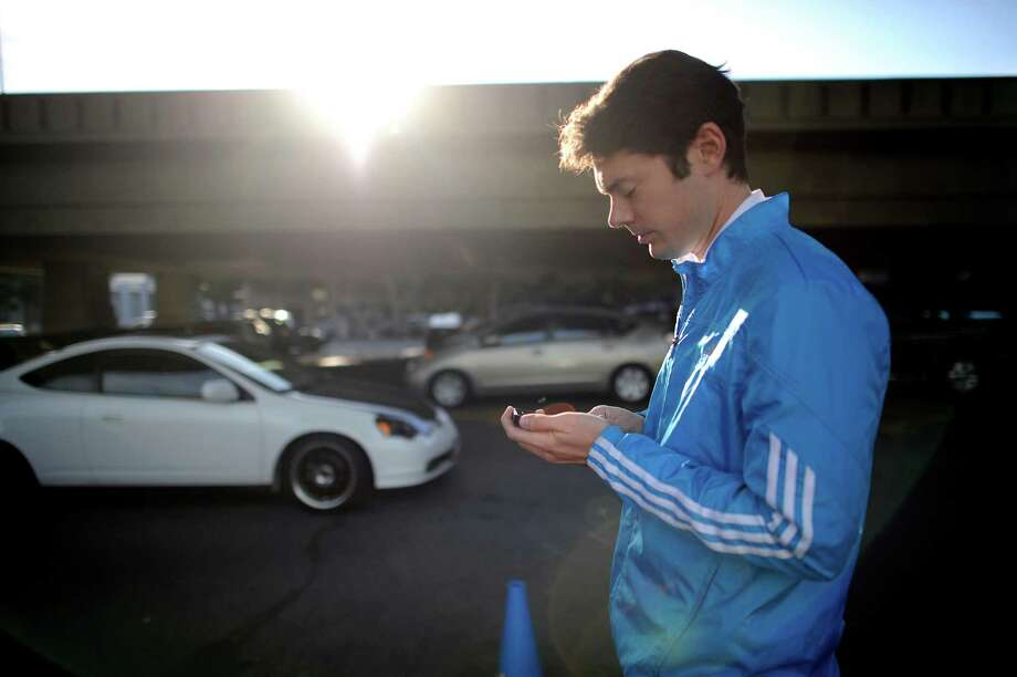 Josh Dunlap checks his phone for nearby customers in one of the Luxe Valet parking lots while working for the on-demand valet service in San Francisco on Oct. 22, 2014. Luxe Valet allows customers to summon a valet with an iPhone app, and the valet meets them wherever they want and drives the car to a secure lot. Photo: Michael Short / Special To The Chronicle / ONLINE_YES