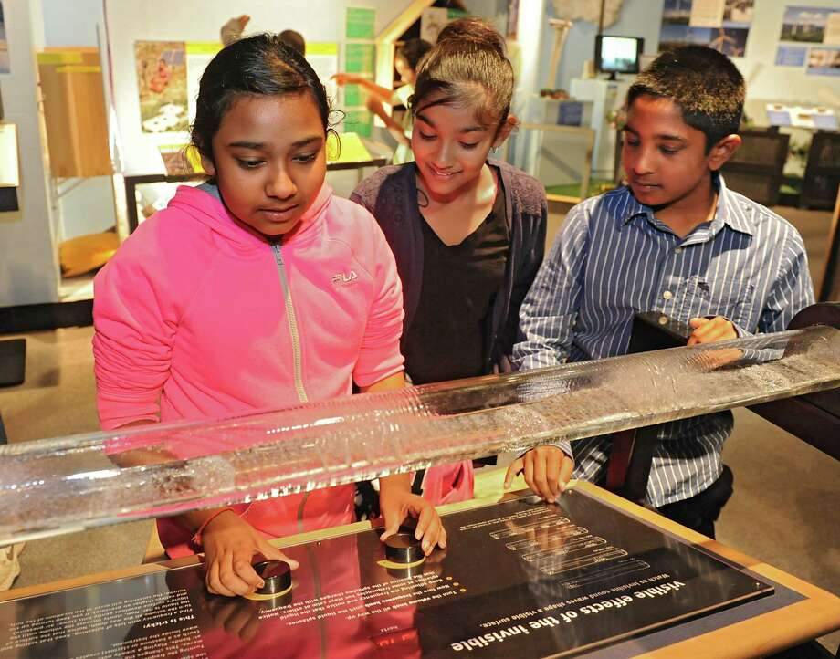 From left, Schenectady children Brianna Dasrat, 10, Melina Roopnarine, 10, and Nyan Panday, 10, watch as invisible sound waves shape a visible surface at the miSci on Wednesday, Oct. 22, 2014 in Schenectady, N.Y. Kids experienced hands-on STEM: electricity demos, nanotechnology activities, planetarium show and interactive exhibits at miSci in partnership with Afterschool Works! (Lori Van Buren / Times Union) Photo: Lori Van Buren / 00029147A