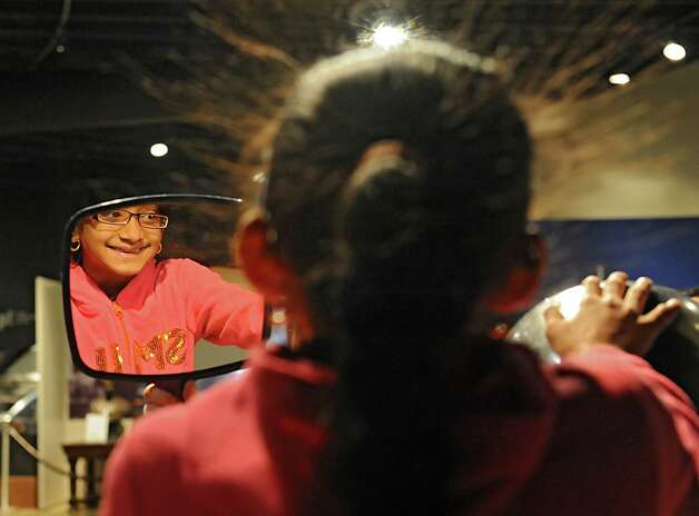 Pria Singh, 9, of Schenectady looks at her hair stand up in a mirror while using the Van de Graaff generator at the miSci on Wednesday, Oct. 22, 2014 in Schenectady, N.Y. Kids experienced hands-on STEM: electricity demos, nanotechnology activities, planetarium show and interactive exhibits at miSci in partnership with Afterschool Works! (Lori Van Buren / Times Union) Photo: Lori Van Buren / 00029147A
