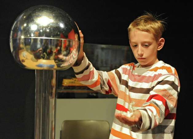 Michael Peltier, 11, of Schenectady waits for his hair to stand and a piece of cotton to fall off his hand while using the Van de Graaff generator at the miSci on Wednesday, Oct. 22, 2014 in Schenectady, N.Y. Kids experienced hands-on STEM: electricity demos, nanotechnology activities, planetarium show and interactive exhibits at miSci in partnership with Afterschool Works! (Lori Van Buren / Times Union) Photo: Lori Van Buren / 00029147A
